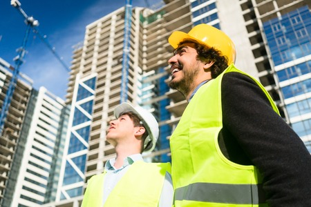 construction project: Architects or civil engineers on large construction site giving instructions