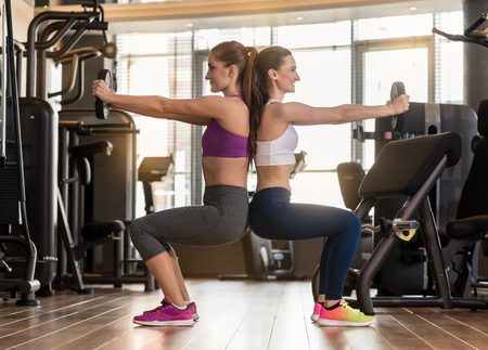 Side view of two young women smiling while exercising together back to back with weight plates in the interior of a modern fitness club Stock Photo