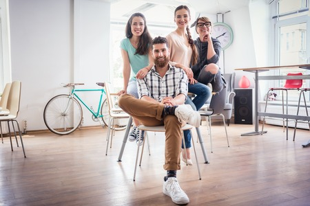 Portrait of four co-workers smiling and looking at camera while wearing cool casual clothes, during work in the shared office space of a modern hub for freelancers and young entrepreneurs Stock fotó - 85646182