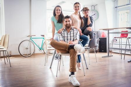 Portret van vier medewerkers die camera lachen en kijken terwijl ze koele casual kleding dragen, tijdens werk in de gedeelde kantoorruimte van een moderne hub voor freelancers en jonge ondernemers