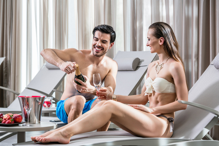 Romantic young man opening a bottle of champagne while relaxing with his partner at the swimming pool in a fancy hotel Stock Photo