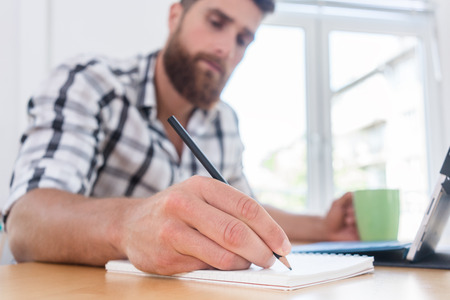 Close-up of the hand of a creative young man holding a pencil over a blank notebook, while thinking of a new project or assignment during freelance work in a co-working space