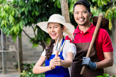 Young Asian couple smiling while working in the garden together