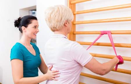 pain: Senior patient doing therapeutic rehabilitation exercises at gymnasium ladder
