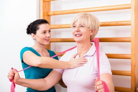 back ache: Senior patient doing therapeutic rehabilitation exercises at gymnasium ladder