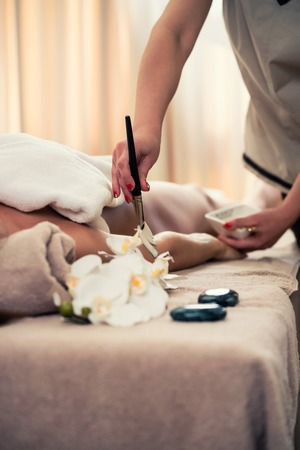 Woman lying down on massage bed during Asian anti-aging treatment with organic moisturizer at beauty center