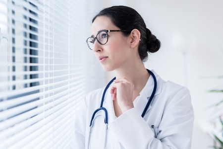 Side view portrait of a young female doctor daydreaming while looking through the window during break in a modern hospital or medical center Stock Photo