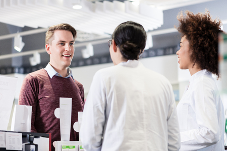 Cheerful young man and happy customer talking with two helpful female pharmacists in a contemporary drugstore with friendly employees Imagens