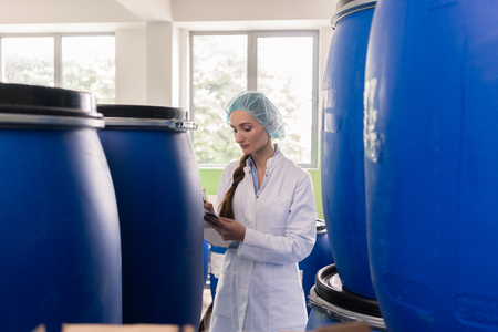 Motivated manufacturing employee writing a report while checking the plastic containers, with liquid cosmetics during quality control in the factory