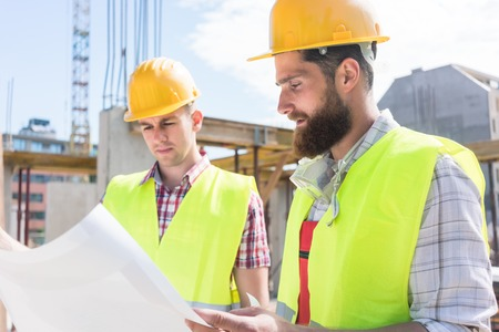 new: Two young construction workers wearing yellow hard hats and reflective safety vests while analyzing together the plan of a new building