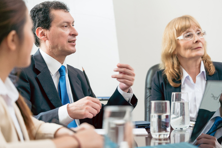 decisionmaking: Side view of an expert businessman sharing his view about the development of an important project during a decision-making meeting in the conference room