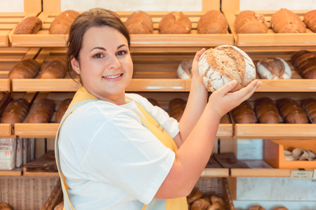 saleslady: Saleslady in bakery shop presenting bread to potential buyer