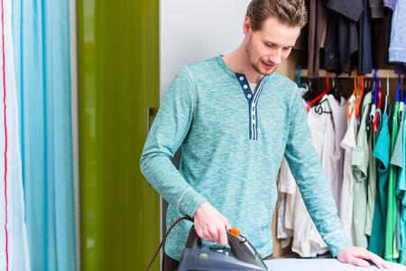 鉄と洗濯物をアイロンのワードローブの前の男 写真素材