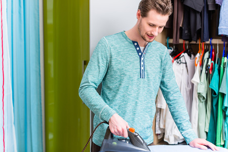 Man in front of wardrobe ironing the laundry with iron