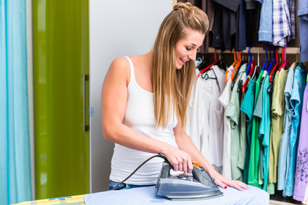 Young woman in front of wardrobe ironing the laundry with iron
