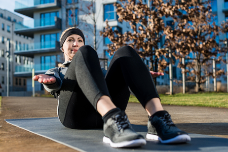 Young woman sitting in an isometric position while doing crunches with raised up palms for the abdominal muscles outdoors in the park Stock Photo