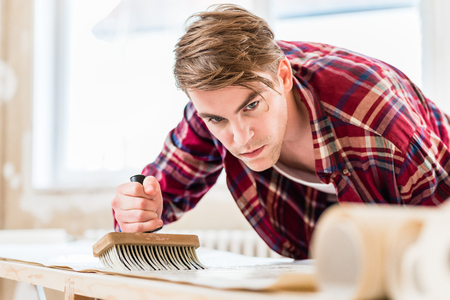 Handsome young man applying paste with a synthetic brush to the surface of a wallpaper sheet during home remodeling Stock Photo