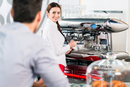 Attractive waitress smiling to male customer while preparing espresso at the automatic coffee machine indoors