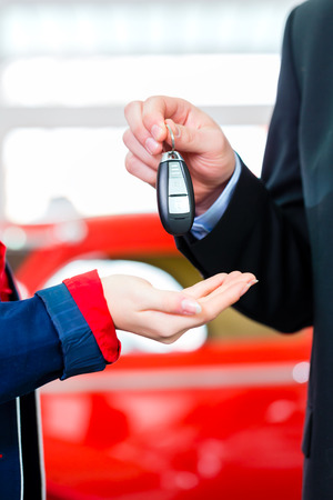 Woman with key to new auto in car dealership