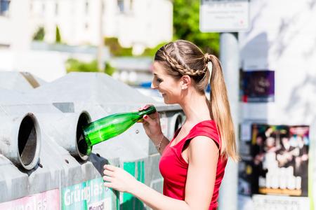 リサイクル センターの容器にペットボトルを投げる女性