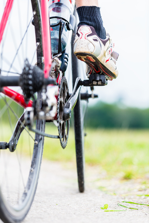 Chain, pedal, rear wheel and sprocket of bike, detail, man having foot on pedal Stock Photo