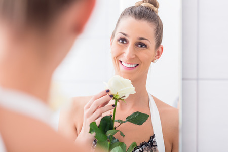 Happily smiling woman holding a white rose and regarding herself in the bathroom mirror Stock Photo