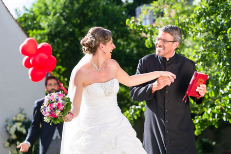 Bride running away with priest after wedding Stock Photo