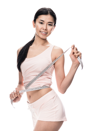 Fit Asian woman smiling while holding measuring tape around her waist