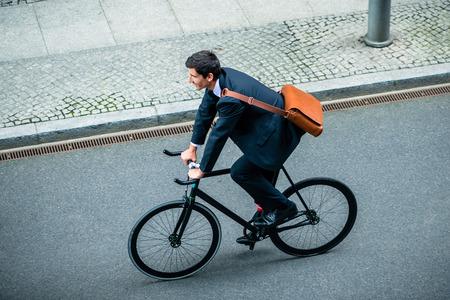 거리에 유틸리티 자전거를 타는 동안 비즈니스 정장을 입고 젊은 남자의 높은 각도보기