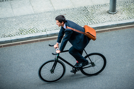 High angle view of young man wearing business suit while riding an utility bicycle on the street