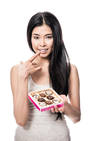 Young Asian woman smiling while holding a box of chocolates against white background
