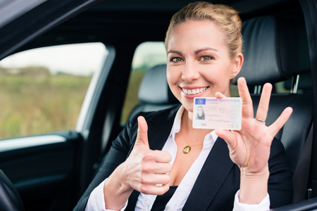 Woman showing driving license and thumbs up Banco de Imagens - 86521413