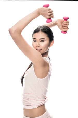 Portrait of fit Asian woman exercising with two small dumbbells against white background