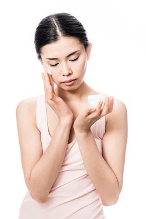 Beautiful young Asian woman applying facial moisturizer cream for sensitive skin care Stock Photo