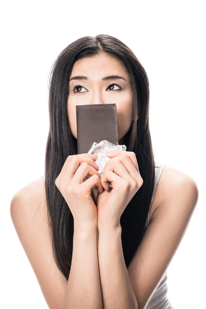 Portrait of young Asian woman looking up while holding a chocolate bar