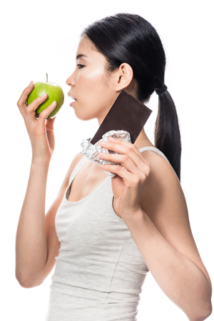 Funny young woman eating a fresh apple while looking at a chocolate bar Stock Photo
