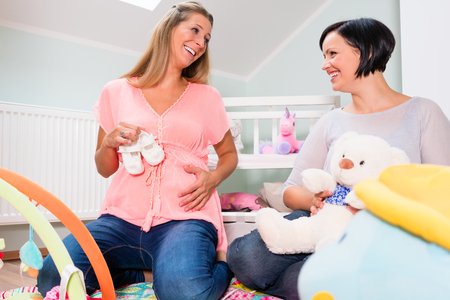 Soon-to-be mum and friend arranging childs room