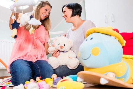 Heavily pregnant woman and friend arranging childs room