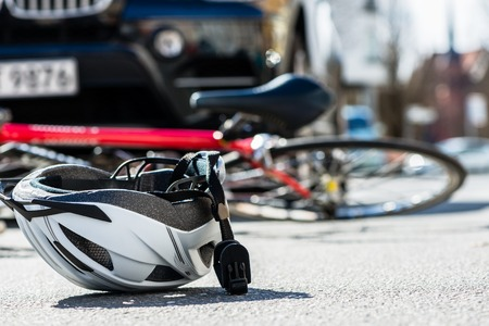 Close-up of a bicycling helmet fallen on the asphalt  next to a bicycle after car accident on the street in the city Archivio Fotografico
