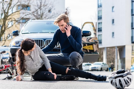 Full length view of a worried young driver calling the ambulance after hitting and injuring accidentally a female bicyclist on a city street Stock Photo