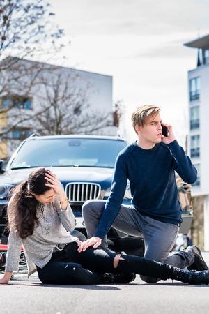 Pełny widok zmartwionego młodego kierowcy dzwoniącego po karetkę po przypadkowym uderzeniu i zranieniu rowerzystki na miejskiej ulicy Zdjęcie Seryjne