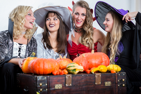 joining forces: Three young and beautiful women wearing funny party costumes while acting as witches joining their malicious forces at Halloween Stock Photo