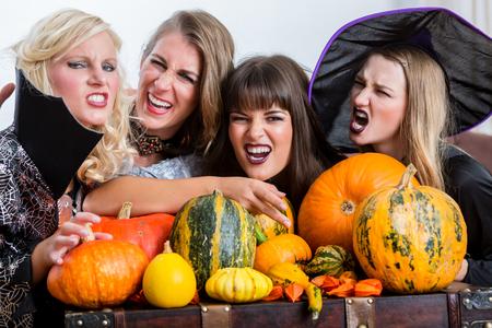 Vier nette Schönheiten, die beim Halloween zusammen während der Kostümpartei zuhause in einem verzierten Raum rösten rösten