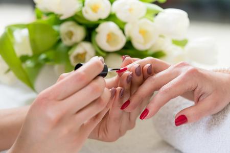 流行の美容室の若い女性の爪の中程度の長さのエレガントな赤のマニキュアを適用する熟練したネイリストの手のクローズ アップ