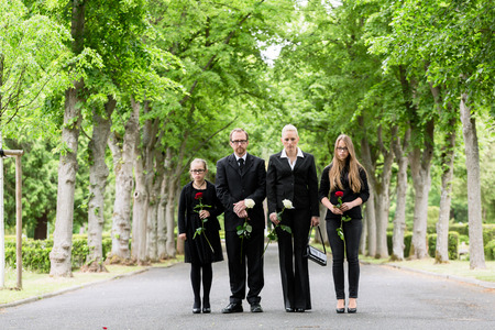 Family on cemetery walking down alley at graveyard with roses