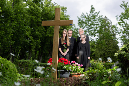 dolor: Family mourning at grave on graveyard or cemetery