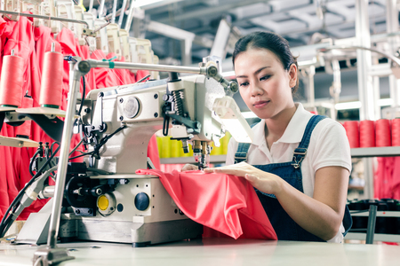 Seamstress or worker in Asian textile factory sewing with  industrial sewing machine Stock Photo