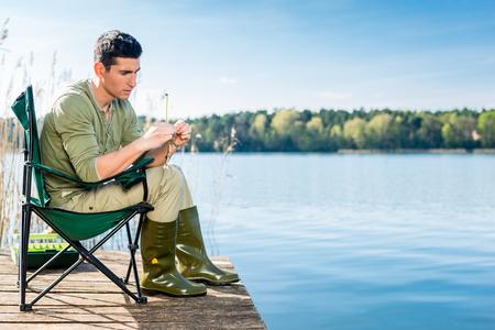 Man fishing at lake fixing lure at angling rod
