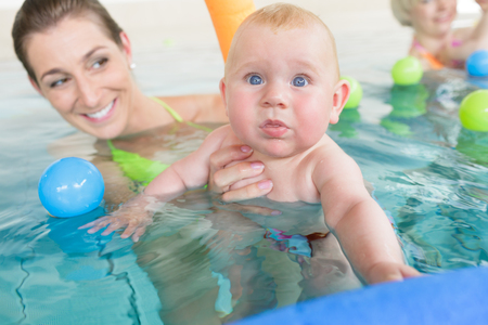 Mothers and their kids having fun at baby swimming lesson between lots of water balls Stock Photo