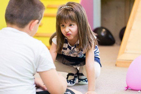 Carino ragazza prescolare fare una faccia buffa mentre guardando un ragazzo con ostilità durante la ricreazione all'asilo Archivio Fotografico - 86811720